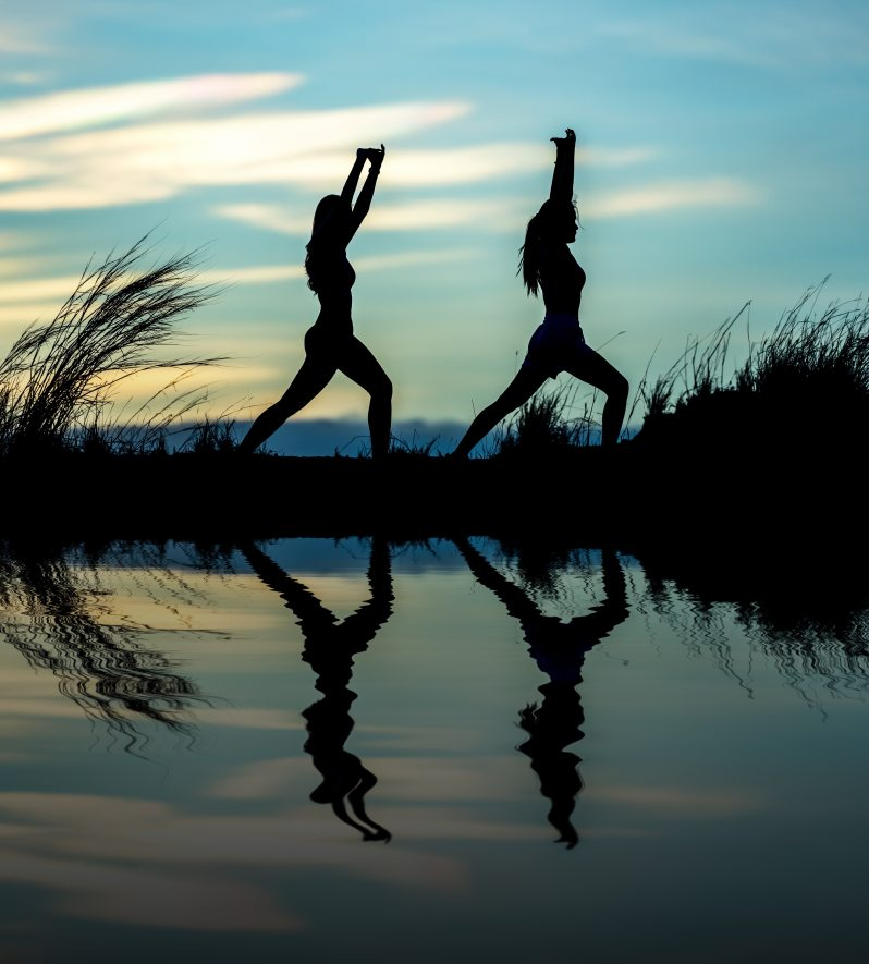 two women stretching silhouetted by a pond