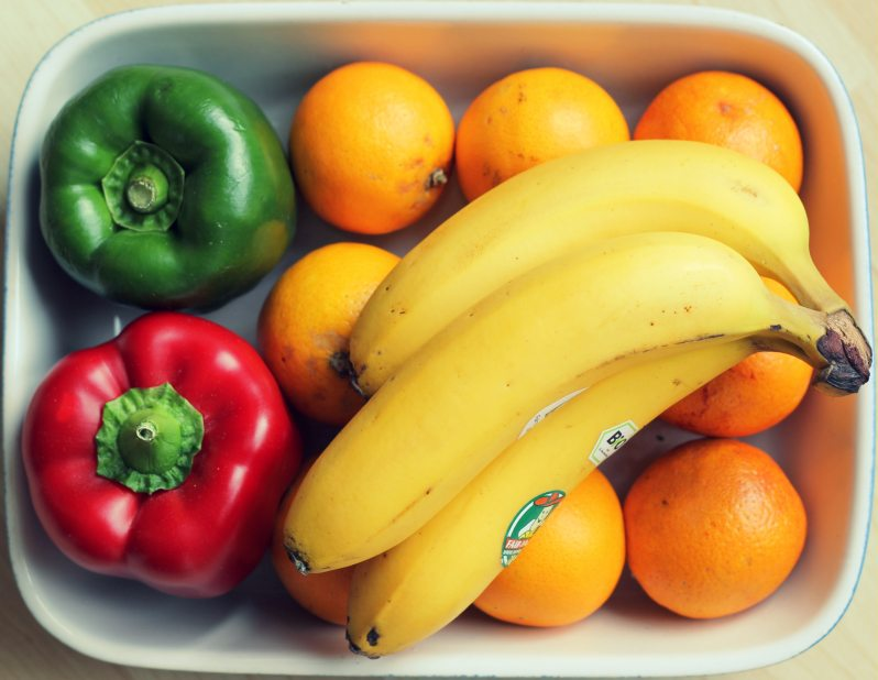 Bananas, oranges, and red and green bell peppers in a bowl