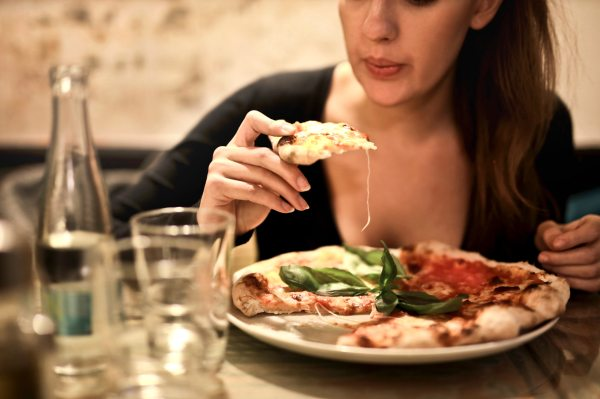 woman at restaurant cooling pizza slice by blowing on it