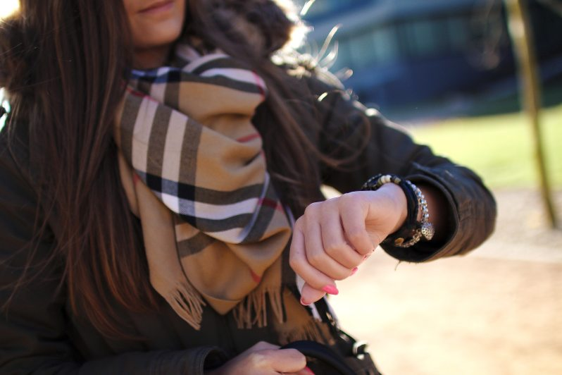 Fashionable woman checking the time on her watch