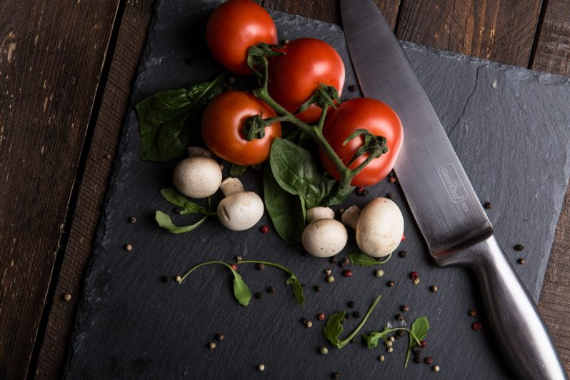 Cutting board with knife, tomatoes, herbs, and mushrooms