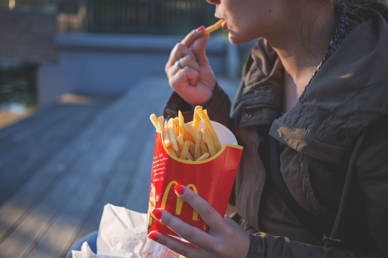 Woman eating McDonald's french fries on an outdoor bench