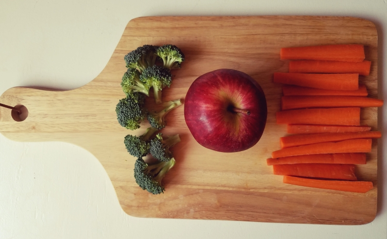 broccoli apple and carrot sticks on a wooden cutting board