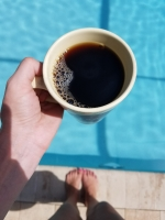 Holding black coffee above blue pool water