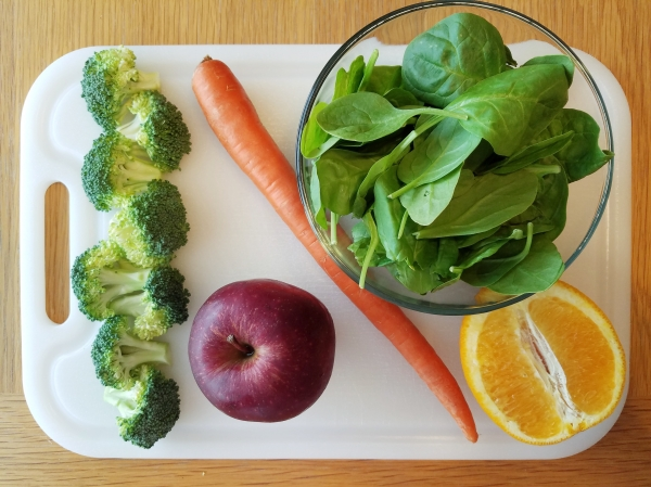 carrot, broccoli, apple, orange, and spinach on white cutting board