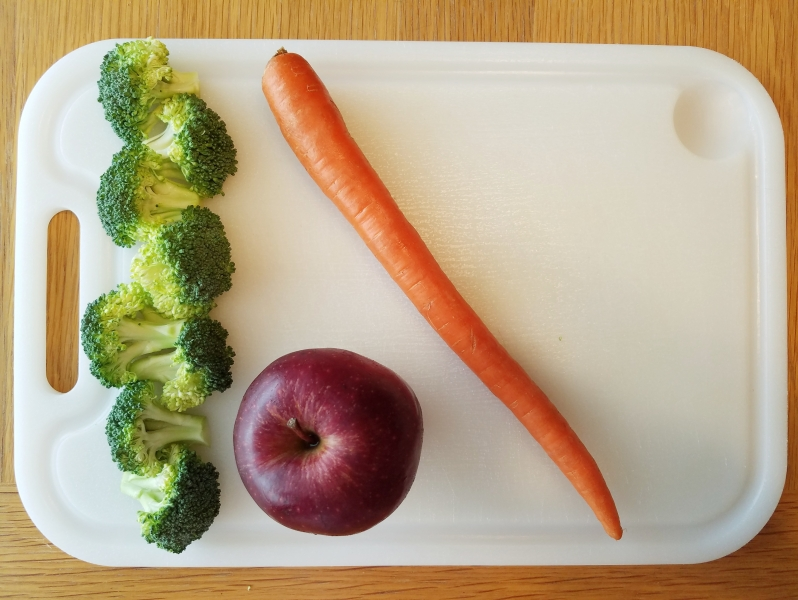 whole carrot, broccoli, and an apple on a white cutting board
