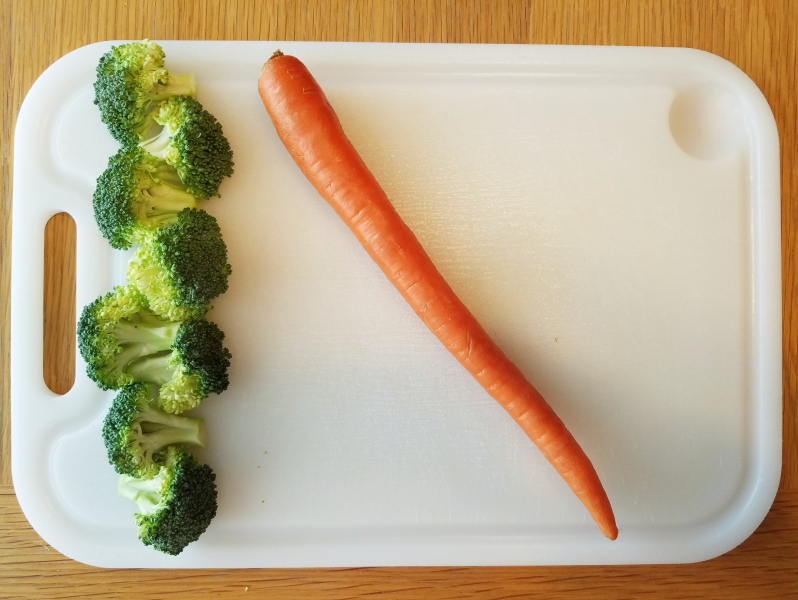 whole carrot and bunch of broccoli on cutting board