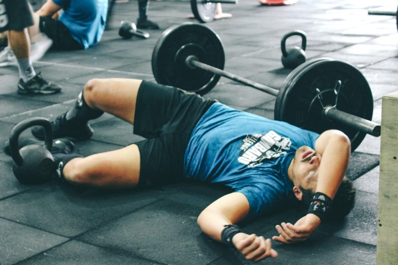 man lying on gym floor next to barbell, exhausted