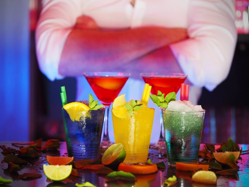 bartender standing behind several fruity drinks