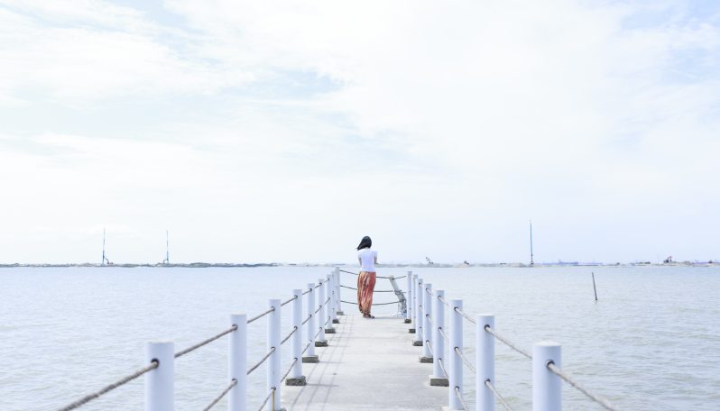 woman standing alone on the end of a pier over the ocean