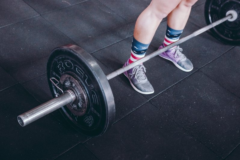 Athlete standing behind a large barbell on the gym floor