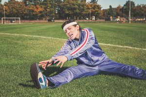 woman in sweatsuit stretching un-enthusiastically on a soccer field