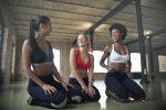 three women in sports bras kneeling in fitness studio