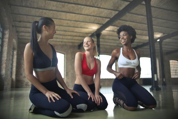 three women in sports bras kneeling in fitness studio