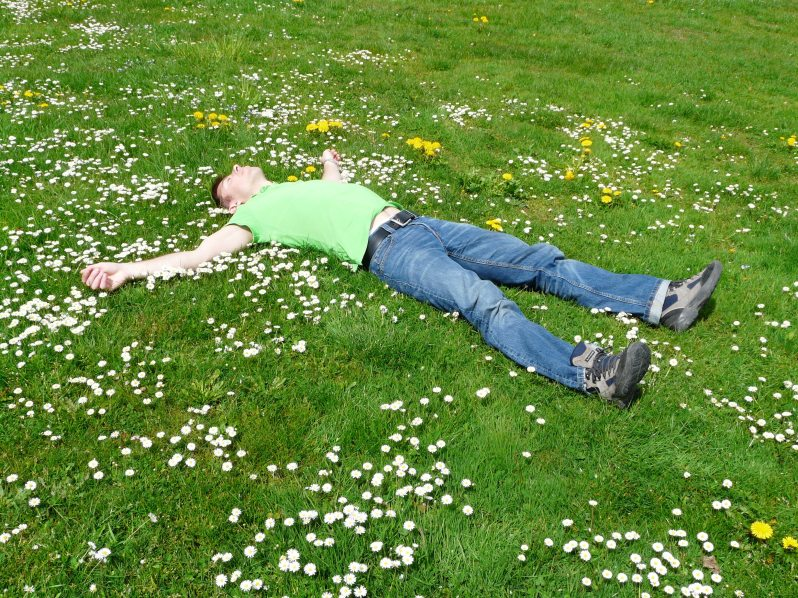 man lying in a field looking at the sky