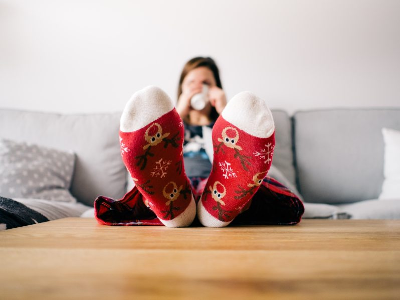 woman sitting on couch, drinking a hot beverage, wearing Christmas socks