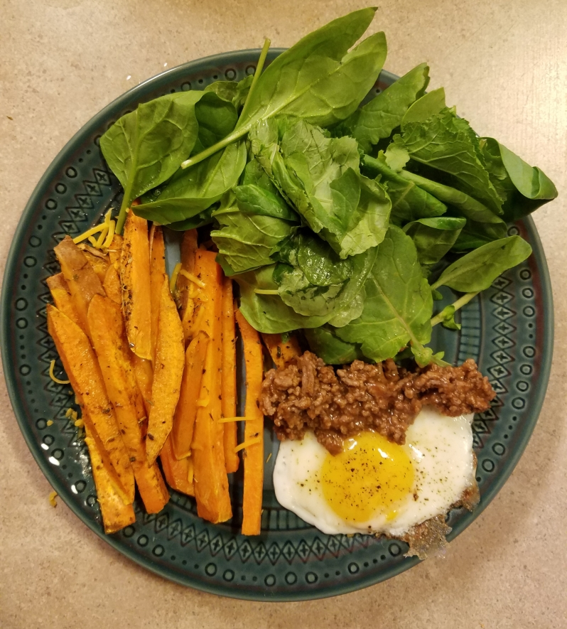Healthy dinner with egg spinach potatoes and beef